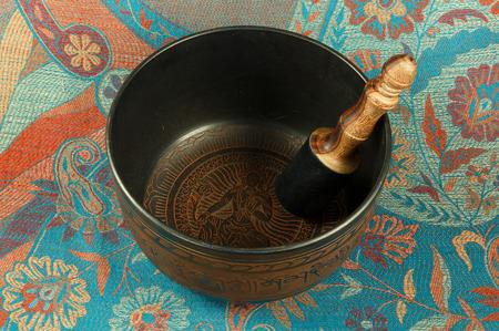 tibet bowls: metal Tibetan singing bowl against the backdrop of Indian fabrics Stock Photo