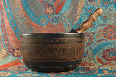 tibetan singing bowl: metal Tibetan singing bowl against the backdrop of Indian fabrics Stock Photo