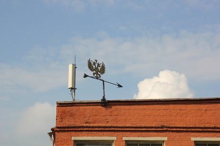 Weather vane in the form of a double-headed eagle symbol of the Russian Empire on the roof photo