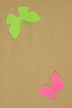 Homemade cardboard butterfly on beige paper. Blank for scrapbooking.