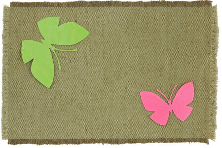 Homemade cardboard butterfly on green coarse cloth. Isolated object on a white background.