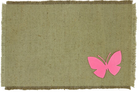 Homemade cardboard butterfly on green coarse cloth. Scrapbook. Background. Isolated object on a white background.