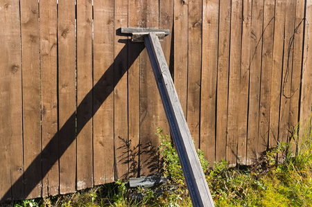 rafter: Fragment of an old fence in an abandoned garden backed wooden beams