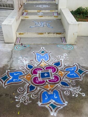 front door: Colorful figure-prayer painted around the front door. Festival rangoli. India