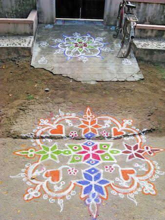 rangoli: Colorful figure-prayer painted around the front door. Festival rangoli. India