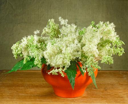 Meadowsweet. 정물. 나무 테이블에 서있는 오렌지 냄비에 초원 꽃의 꽃다발. 소박한 스타일.