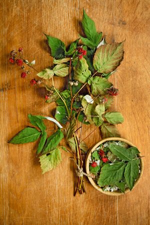 phytotherapy: Raspberry.Dried herbs for use in alternative medicine.Herbal medicine, phytotherapy medicinal herbs.For preparation of infusions, decoctions, tinctures, powders, ointments, tea.Background wooden board