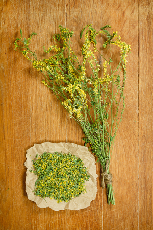 phytotherapy: Melilot.Dried herbs for use in alternative medicine.Herbal medicine, phytotherapy medicinal herbs.For preparation of infusions, decoctions, tinctures, powders, ointments, tea.Background wooden board