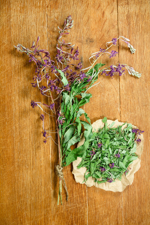 phytotherapy: Fireweed.Dried herbs for use in alternative medicine.Herbal medicine, phytotherapy medicinal herbs.For preparation of infusions, decoctions, tinctures, powders, ointments, tea.Background wooden board Stock Photo