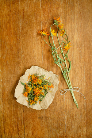 phytotherapy: Calendula.Dried herbs for use in alternative medicine.Herbal medicine, phytotherapy medicinal herbs.For preparation of infusions, decoctions, tinctures, powders, ointments, tea.Background wooden board Stock Photo