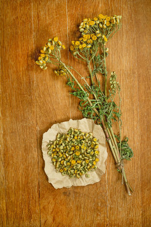 phytotherapy: Tansy.Dried herbs for use in alternative medicine.Herbal medicine, phytotherapy medicinal herbs.For preparation of infusions, decoctions, tinctures, powders, ointments, tea.Background wooden board