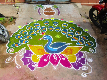 Colorful figure-prayer painted around the front door. Festival rangoli. India