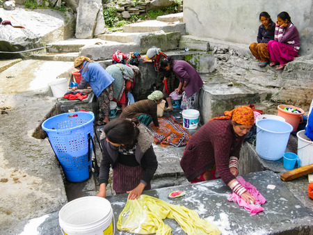 VASISHTA VILLAGE, CITY OF MANALY, STATE HIMACHAL PRADESH, INDIA - APRIL 18, 2014: Women wash clothes at the source. in a small village in the Himalayas in the north of the state Himachal Pradesh. Editorial