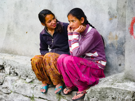 VASISHTA VILLAGE, CITY OF MANALY, STATE HIMACHAL PRADESH, INDIA - APRIL 18, 2014: Two Indian girls are sitting at the source in a small village in the Himalayas in the north of the state Himachal Pradesh.