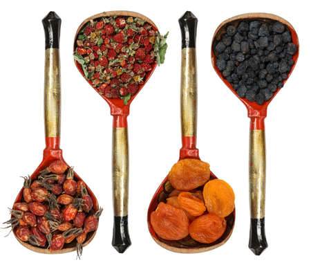 Set of fruits and dried herbs with high content of antioxidants, minerals and vitamins. Strawberry, dry apricot, rosehip, blueberry. Spoons on white background. Flat layout. Alternative medicine.