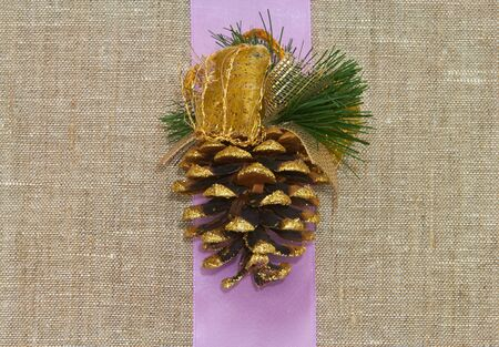 seed beads: pine cone with purple silk ribbon Stock Photo
