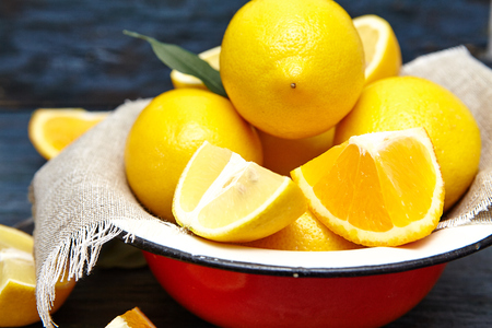 lien: Fresh lemons and oranges in an old plate with linen napkin . dark blue background . Stock Photo