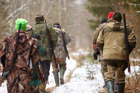 森を歩いているハンターのグループ。冬の狩猟