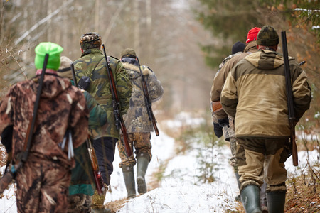 Group of hunters walking in the forest. Winter hunting Standard-Bild