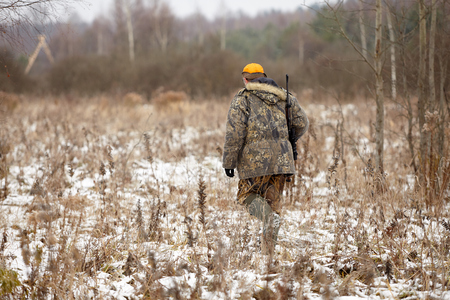 Hunter in camouflage clothes with hunting rifle during a winter hunting