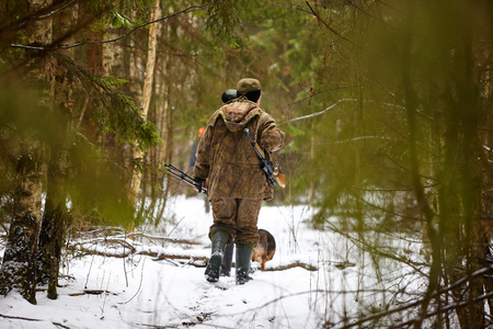 Hunter in camouflage with rifle. Winter hunting.