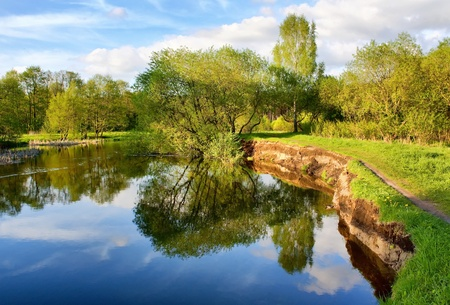 Beautiful riverside view with clouds and trees reflections photo