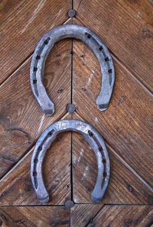 Two lucky horseshoes on wooden wall photo