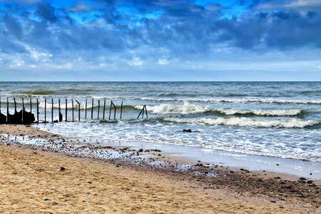 Beautiful sandy beach and the old rusty breakwater photo