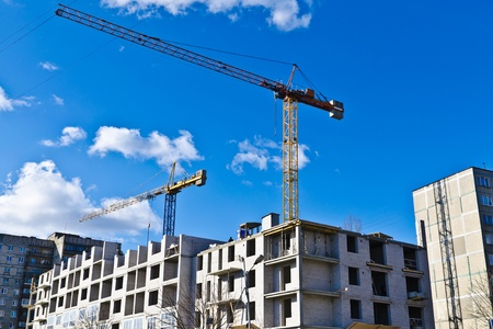 permission granted: Building crane on the background of blue sky and of the house under construction