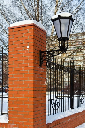 redbrick: Beautiful street lamp at the red-brick wall under the snow Stock Photo