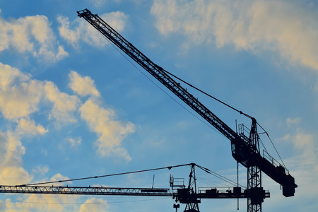 Silhouettes of construction cranes on the sky photo