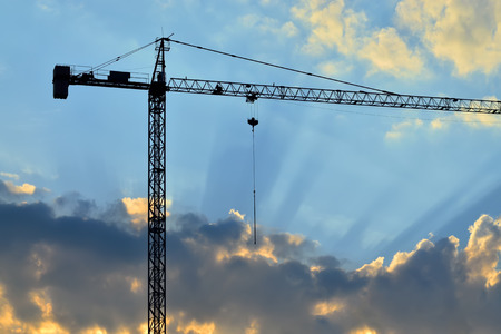 Silhouette of construction crane and the rays of the sun photo