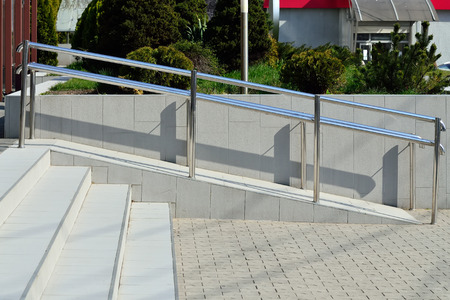 handrails: Ramp for wheelchair entry with metal handrails