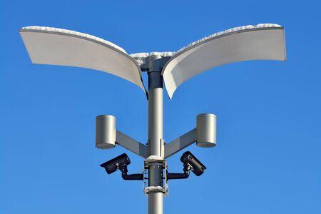 fixtures: Surveillance cameras and modern lighting fixtures on the lamppost Stock Photo