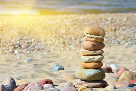 Pyramide von Kieselsteinen an einem sonnigen Strand Lizenzfreie Bilder