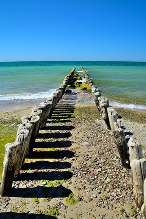 Breakwater on the beautiful sandy beach of the Baltic sea in sunny day Standard-Bild