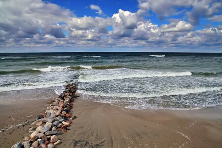 Old breakwater on the sandy beach of the Baltic sea in Sunny summer day