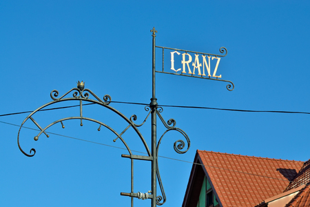 Pointer to the old name of the city Cranz on the background of blue sky and tiled roofs. Zelenogradsk (until 1946 - Cranz), Kaliningrad oblast, Russia