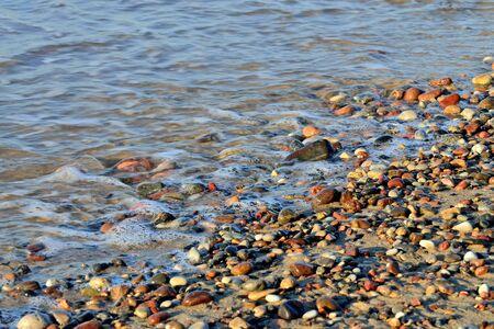 Colorful pebbles on a Sunny beach and sea surf Standard-Bild