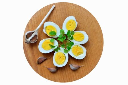 Boiled eggs with arugula sprigs and garlic closeup on a chopping Board