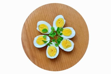 Boiled eggs with arugula sprigs are on the cutting Board Stock Photo