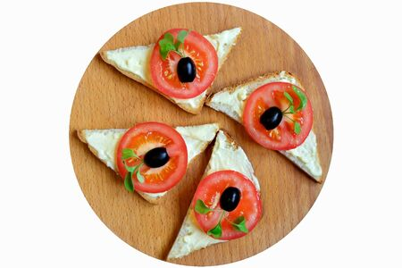 Sandwiches with red tomato, olives and arugula on the cutting Board Stock Photo - 145665558