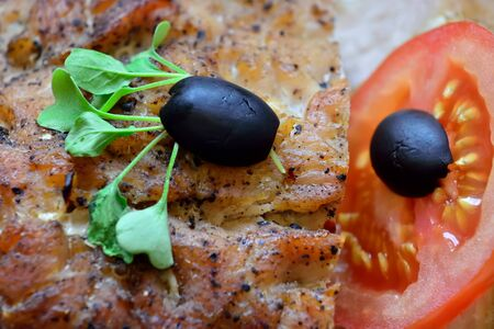Delicious baked meat with tomato, olives and arugula is on the plate Stock Photo - 145665556