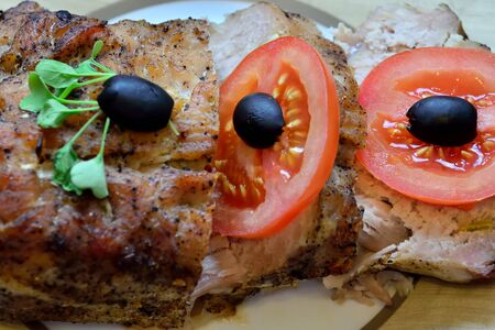Delicious baked meat with tomato, olives and arugula is on the plate Stock Photo