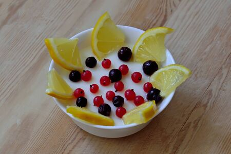 Milk mousse with black and red currant berries and lemon in white bowl