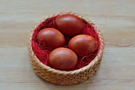 Beautiful dyed chicken eggs lie in a wicker basket Stock Photo