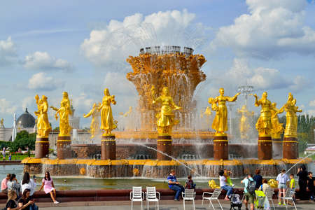 Moscow, Russia - August 25, 2020: tourists inspect the fountain Friendship of Peoples with golden statues, the main fountain and one of the main symbols of VDNH