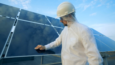 Male engineer cleans solar panel.