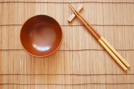 Chopsticks with wooden bowl on bamboo matting background