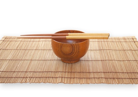 Chopsticks with wooden bowl on bamboo matting background  photo